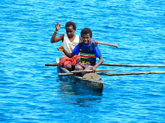 4. Vanuatu girls fishing in a dugout canoe